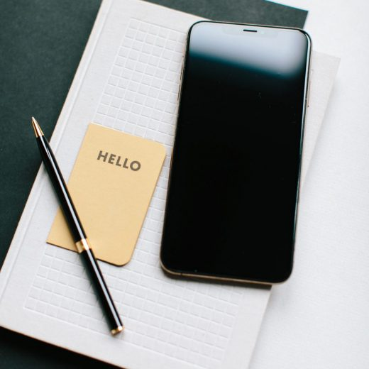 photo of a phone pen and paper with the words hello